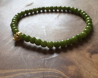 Olive and Gold Skull: an elastic beaded bracelet with goldtone skull and olive green glass beads.