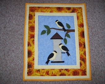 Yellow finches at the bird feeder this summer. Machine applique and quilted with a sunflower border.