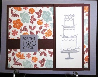 Handmade Wedding Card featuring tiered wedding cake with lovebird topper, in lavender, raspberry and floral pattern