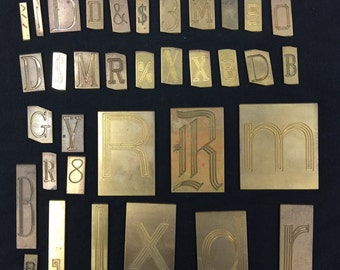Collection of 35 vintage brass engraving plates various sizes and letters numbers symbols.