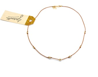 Simple necklace in natural silk thread with beads and clasp plated gold