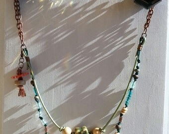 The Carrot Gardener beaded necklace of leather cording, handmade glass carrot beads with antique copper