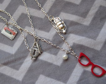 Madeline Ferguson necklace, inspired by Twin Peaks, with red glasses, cassette tape, and microphone charms.