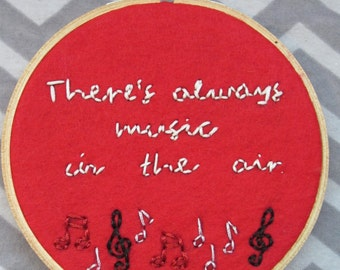 There's Always Music In The Air embroidery hoop, art inspired by Twin Peaks. Glow In The Dark words, metallic Music Notes.