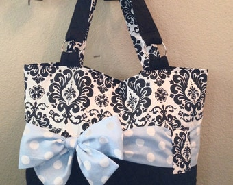 Personalized Diaper Bag In Black And White Damask With Blue And White Polka Dot Bow/Sash.  Add On The Matching Changing Pad.