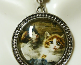 Two cats on a blue blanket pendant with chain - CAP26-048