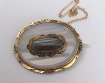 Antique, Victorian mourning brooch in chalcedony and gold metal with a plaited hair insert, complete with a safety chain.