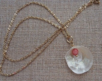 this necklace is a shell with coral bead inside on gold chain