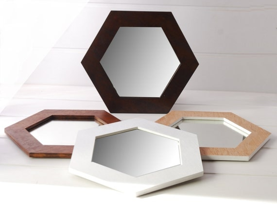 white hexagonal mirror wooden on the wall On miroir hexagonal
