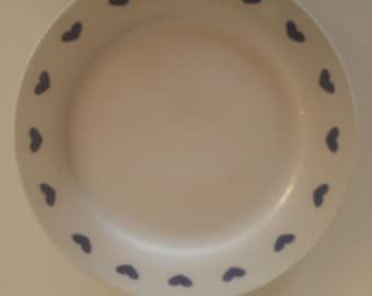 12 inch porcelain dinner plate with heart patterns and shapes around the rim.