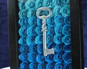 Silver key on handmade blue paper flowers