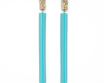 Handmade large long chandelier drop facet geometric statement dangle resin earrings in gold glitter and turquoise blue.