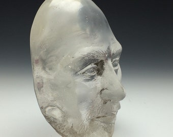 Glass art portrait face of a man, sand cast lens head, optical art suncatcher paperweight bust