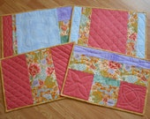PLACEMATS QUILTED PASTEL Set of four in Lavender Peach Green Blue Green and Gold with a hint of Oriental flavor.
