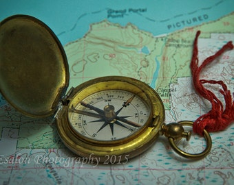 Photograph of an old vintage compass on a color map of Michigan Pictured Rocks color print
