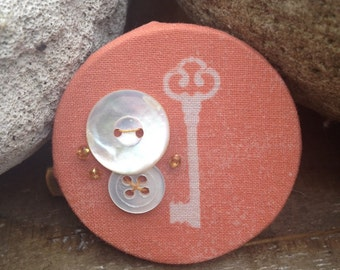 Orange key brooch, cyanotype sunprint with mother of pearl button detail