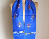 This a long silk Francoise Guerin scarf.  It is a royal blue color with a boating theme--anchors and ropes