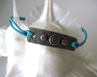 Bracelet.  silver medallion on aqua leather