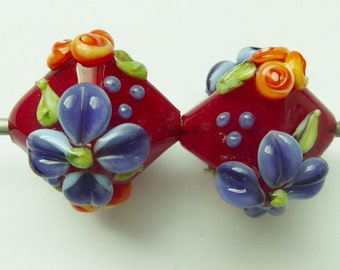 Glass lampwork beads in red with flower decoration.