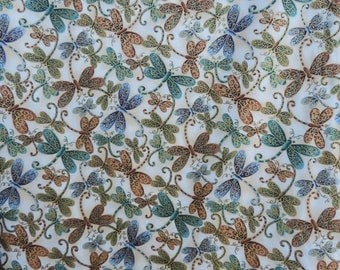 Multi-colored dragonflies on cream colored background.