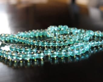 130 approx. 6 mm drawbench transparent glass beads, sea glass green, with spray painted white lines, hole 1.3-1.6 mm