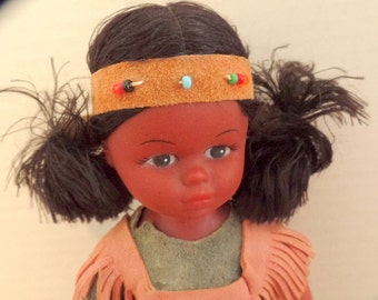 Vintage, old style Native American souvenir doll.  She is made of vinyl, and dressed in a suede costume, and moccasins