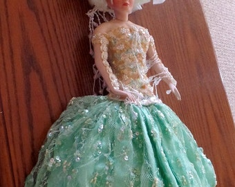 Showstoppers all porcelain showgirl doll.  She is wearing a green satiny skirt, and yellow/green bodice