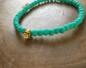 Aqua Gold Skull: an elastic beaded bracelet with gold skull and matte turquoise / teal glass beads.