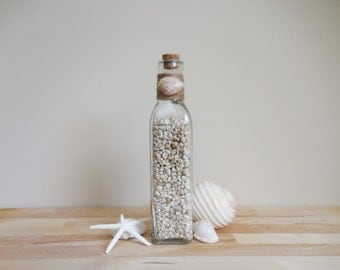 Corked glass bottle filled with venetian pearl shells