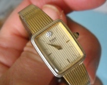 1980's Ladies gold tone rectangular face Pulsar watch with 1 diamond at noon, gold bracelet and face