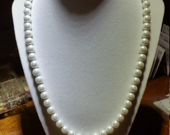 white pearls with a peach flower