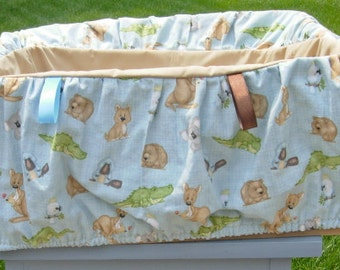 Beige seat with baby animals shopping cart cover for toddlers or babies.