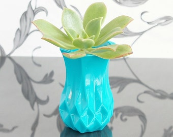 Vintage cut glass style resin bud vase in turquoise blue.