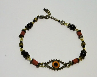 Bronze tone metal Enameled Eye Bracelet with Glass and Terracotta Beads.