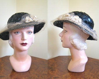 1930s black hat in glossy raffia, with beautiful peach net and velvet flowers