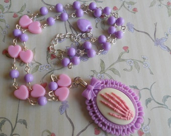 Pink skeleton hand necklace with purple and pink beads