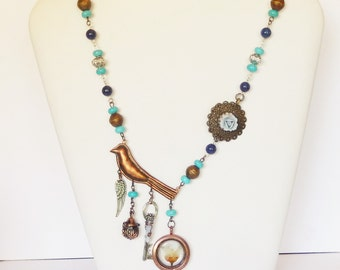 Mixed metal Assemblage art necklace with a copper bird and locket, real flower in resin, a key and Agate, Turquoise beads and Lapis beads