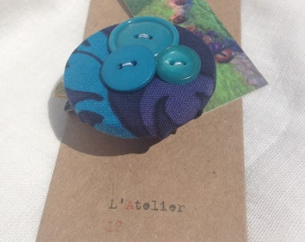 Vintage blue fabric brooch with button detail.