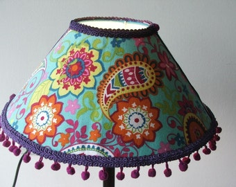 Lovely Colorful standing table lamp with paisley,  flowers and purple pom-poms on  turquoise background