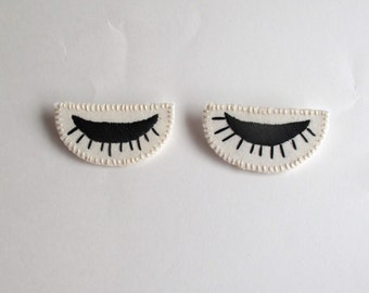 Eye brooch hand embroidered in black on cream muslin and cream felt winking eyes Spring fashion party favor listing is for ONE brooch