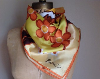 Lovely blend of yellows and browns in this Beeline square scarf with a flower theme.