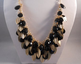 3 Row Bib Necklace with Black Teardrop Beads and Gold Leafs on a Gold Tone Chain