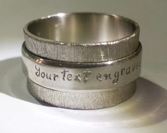 Silver ring with engraved personalized text.