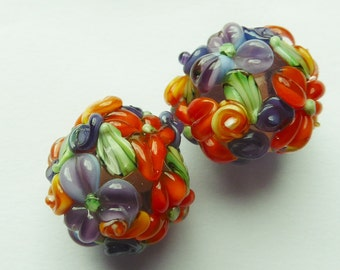 Glass lampwork bead set in purple with raised flower decoration.