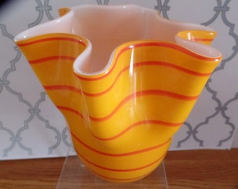 Vintage glass vase with wide mouth, wavy top.  It is milk glass inside, and light orange with darker orange stripes