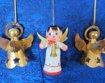 Vintage Christmas Tree Ornaments Circa 70-80s.Two gold tone metal angels wearing a cloak with star cutouts throughout. One angel solid wood.
