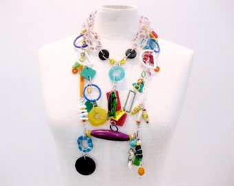composite materials necklace: rubber, resin, paper, ceramic, wood.  Three distinct strands, worn as one necklace.  Colorful.