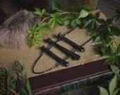 reserved // ascent // gunmetal coyote bone ladder necklace