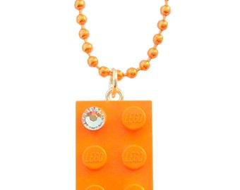 Orange LEGO (R) brick 2x4 with a Diamond color SWAROVSKI crystal on a Silver/Gold plated trace chain or on an Orange ballchain
