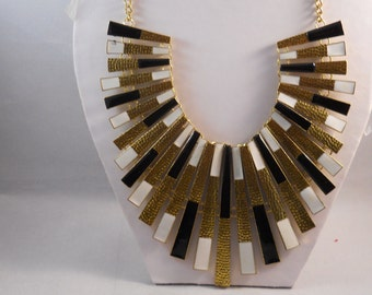 Bib Necklace with With Black, White and Gold Pendants on a Gold Tone Chain
